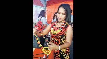 KREATIF: Lucy menunjukkan hasil unik kraf manik perhiasan wanita suku kaum Bidayuh Jagoi yang dibuatnya sendiri untuk lensa Utusan Borneo.