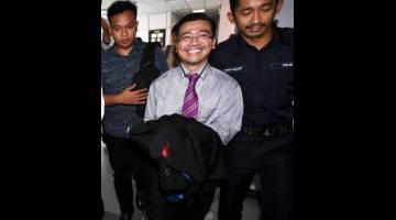 TERTUDUH: Azizan (tengah) dihadapkan ke Mahkamah Sesyen semalam, atas tuduhan menerima suapan bernilai RM25,000 membabitkan pemberian kontrak menaik taraf cerun dan parkir berbumbung Bangunan JKR Daerah Kulai pada 23 Oktober 2015. — Gambar Bernama