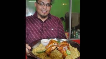 GAMIT TUMPUAN: Zulhasnan menunjukkan antara menu Nasi Arab Asli berasaskan Ayam Golek yang disediakan untuk para pelanggan yang datang untuk menjamu selera di Gong Nering Besut sempena bulan Ramadan ini. — Gambar Bernama