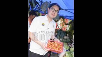 JUNZ menunjukkan sayur-sayuran segar di pasar tani yang dibuka sempena sambutan Pesta Kobis di Kg Kiau, Kundasang.