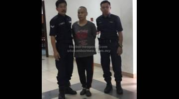 DIADILI: Bandang diiringi polis di pekarangan Mahkamah Kuching semalam.