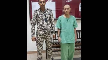 LAPORAN BELUM SIAP: Alister diiringi pegawai penjara di lobi mahkamah semalam.