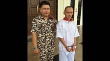 MENTAL SIHAT: Alister diiringi pegawai penjara di pekarangan Mahkamah Kuching semalam.