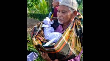 DISEMADIKAN: Hassan membawa jenazah cucu saudaranya untuk dikebumikan ke Tanah Perkuburan Islam Kampung Lembah di Pasir Puteh semalam. — Gambar Bernama