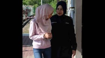 KE MUKA PENGADILAN: Anggota polis mengiringi Nurul Yasmin selepas di tuduh atas kesalahan menipu umrah di Mahkamah Majistret 3 Sungai Petani semalam. — Gambar Bernama