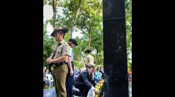 PERINGATAN: Andrew Goledzinowski (kanan) meletakkan kalungan bunga di tugu Taman Peringatan Sandakan pada majlis Hari Memperingati Sandakan semalam. — Gambar Bernama
