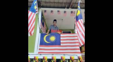 BANGGA: Malaysia Sahat dari Kampung Endap berdiri di anjung rumahnya yang dihiasi dengan warna-warni bendera yang menunjukkan semangat patriotiknya.