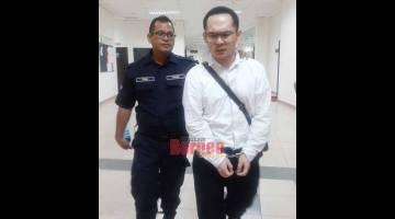 DIBICARA: Wong Zing Haw ketika menuju ke bilik tahanan Mahkamah Kuching.