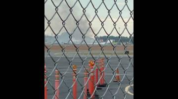 TERHEMPAS: Asap dilihat dari tapak sebuah pesawat vintaj terhempas di Lapangan Terbang Antarabangsa Bradley, Connecticut, Amerika Syarikat kelmarin. — Gambar Bryan St. Amand/Reuters