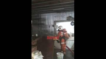 PADAM: Anggota bomba berusaha memadamkan kebakaran di premis terbabit.