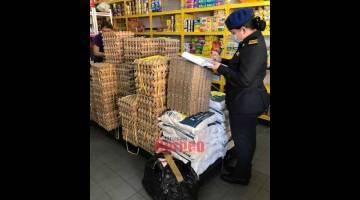 PANTAU: Pegawai penguat kuasa KPDNHEP Sarawak memeriksa satu daripada premis perniagaan di pasar Simunjan.