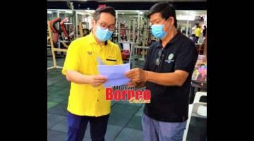 SATU HARAPAN: Chia (kanan) menyampaikan memorandum SOP kepada Tiang di Sibu semalam.