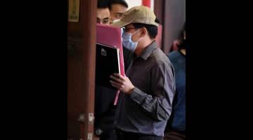 RASUAH: Peguam kanan persekutuan Lim, (bertopi) dihadapkan di Mahkamah Sesyen dekat Butterworth, semalam, atas dua pertuduhan meminta rasuah pada Mac dan Jun lepas. — Gambar Bernama