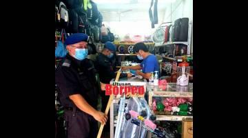 MATAU: Raban penerit adat KPDNHEP lebuh bejalaika pengawa meresa ba sebuah kedai di Sibu, kemari.