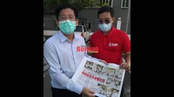 Julian (kiri) dan Anthony menunjukkan keratan akhbar yang memaparkan acara di mana berlakunya penyerahan bendera parti serta poster seakan kertas mengundi.