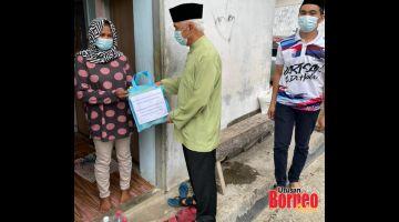 SUMBANGAN AIDILFITRI: Dr Yusop (tengah) diiringgi Mohd. Sharif (kanan) menyampaikan sumbangan Aidilfitri kepada seorang penduduk di Kg. Gadong.
