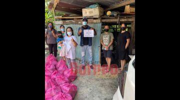 SUMBANGAN: Ijok (tengah) semasa mengagihkan bantuan bakul makanan sumbangan KJRI KK di Sandakan.