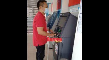 MESRA OKU: Isak menggunakan fon telinga untuk membuat transaksi di mesin ATM 'bersuara' yang disediakan di Hong Leong Bank di pusat bandar raya Kuching.