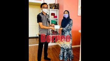 SERAHKAN:Mizma (kanan) menyerahkan sumbangan kepada salah seorang penerima dalam satu majlis yang diadakan di pejabat beliau.